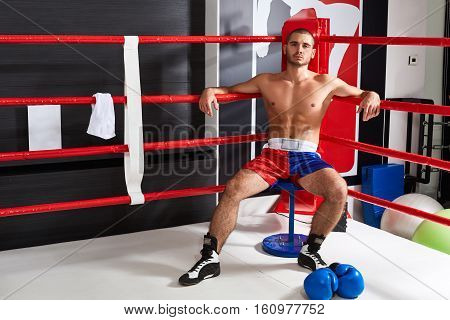 Tired male boxer sitting in the corner of the ring after a hard workout. He looks into the camera