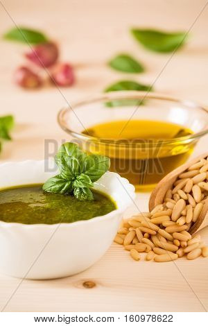Closeup of pesto genovese sauce with fresh basil and pine nuts on a table