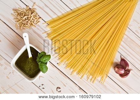 Pesto genovese and linguine pasta pine nuts and garlic on a table seen from above