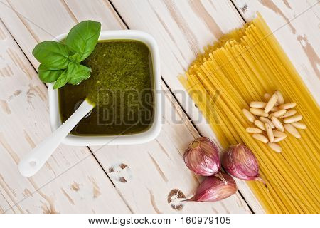 Closeup of pesto genovese and linguine pasta pine nuts and garlic on a table seen from above