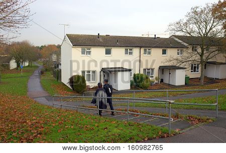 Bracknell,England - December 09, 2016: Pedestrians walking down steps in front of a row of houses on a housing estate in Bracknell, England on a cloudy, December day