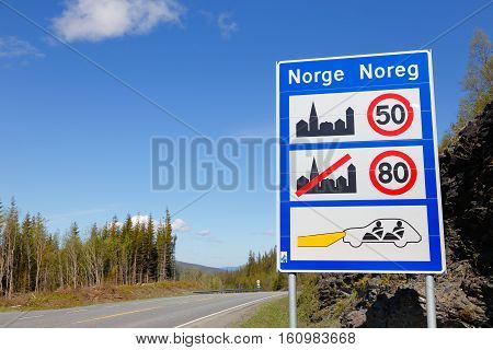 Information board on arrival to Norway indicates the speed in and out of villages and that the seatbelt is used and low beam to be switched on