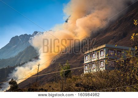 Smoke billows from forest fire burning on a hill in the Lachung village town, Sikkim India.