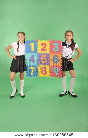 Two school girls hold color board with the number one two three four five six seven eight nine on green