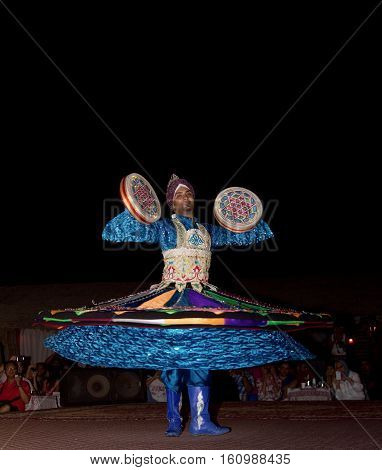DUBAI, UAE - APRIL 20 2012: A local citizen performing traditional folk dance at night as part of a desert safari camp experience