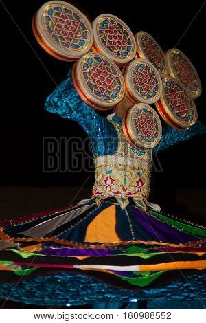 A local citizen performing traditional folk dance at night as part of a desert safari camp experience in Dubai, UAE