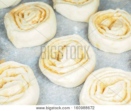 Closeup Of Raw Cinnamon Roll And Cinnamon Buns On Baking Paper