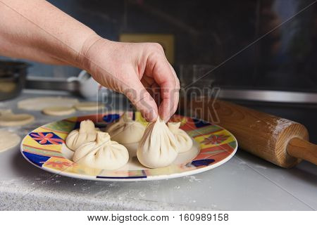 National Georgian cuisine Khinkali. Senior woman prepares khinkali. Top view raw meat dough dish uncooked. Process cooking