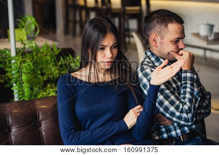 Couple sitting at cafe during lunch. They are taking offense and sitting back to back.