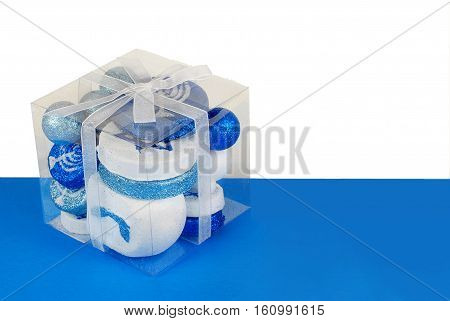 Sparkling Hanuakkah decorations in a clear plastic gift box tied with a white ribbon on a blue and white background. Copy space right side