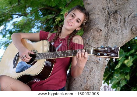 Pretty hispanic teenage girl playing an acoustic guitar sitting on a tree branch