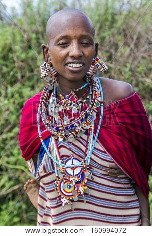 AFRICA, KENYA, MAY, 5, 2016 - Portrait of a woman of the Maasai Mara tribe with traditional dress and jewelry from beads and with a small child behind in Kenya, Africa