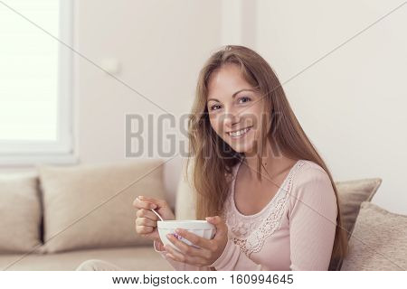 Young woman sitting on a living room couch holding a bowl of cereal and having breakfast