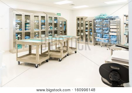 Wide view of a storage room with clean and sterile medical instruments and clothing in a hospital poster