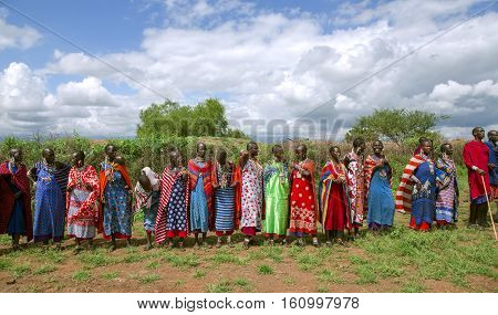 AFRICA, KENYA, MAY, 5, 2016 - Group women of Maasai tribe, many with small children behind, dressed in bright red blankets and ornaments from beads posing for tourists in Kenya, Africa
