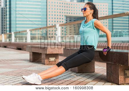 Fit woman doing triceps bench dips exercise while listening to music in headphones. Fitness girl working out in the city.
