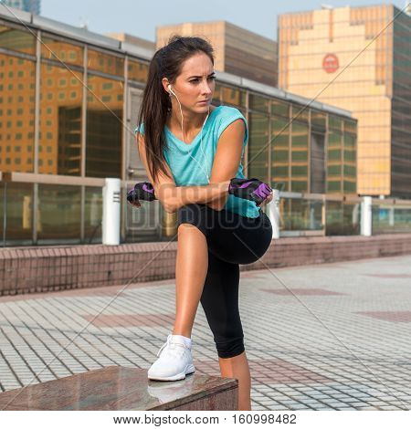Young fit woman taking a break after exercising or running. Fitness girl standing and resting outdoors on city street