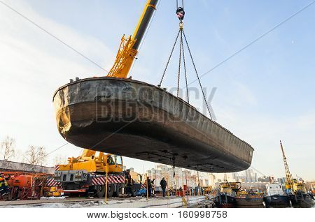 MOSCOW, RUSSIA - NOVEMBER 11, 2016: State Unitary Enterprise Mosvodostok performs recovery vessels on coastal winter parking. Car crane lifts the barge.
