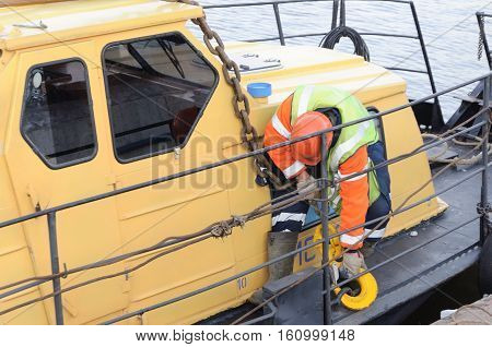 MOSCOW, RUSSIA - NOVEMBER 11, 2016: State Unitary Enterprise Mosvodostok performs recovery vessels on coastal winter parking. Work secures the chain sling on the lug.
