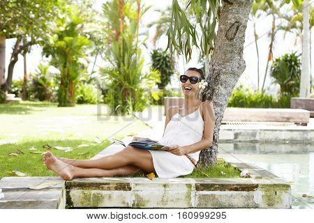 Pregnancy And Happiness Concept. Beautiful Young Expectant Mother In White Dress Relaxing Near Swimm