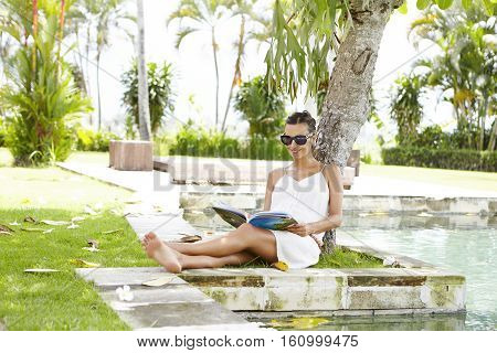 Young Mother Expectant Wearing Shades Having Rest Under Tree With Magazine In Her Hands During Vacat