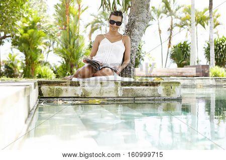 Joyful Pregnant Woman Wearing Trendy Sunglasses And White Dress Reading Magazine, Sitting At Swimmin