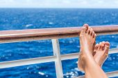 Relaxation on cruise ship travel holiday. Closeup of women feet up on balcony overlooking ocean view on caribbean vacation at sea. Barefoot woman sun tanning relaxing at outdoor spa. poster