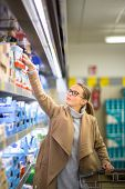 Beautiful young woman shopping for groceries and fruits and vegetables in produce department as well as some lactose free diary products in a grocery store/supermarket (color toned image; shallow DOF) poster