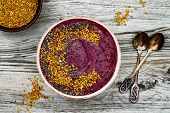 Acai breakfast superfoods smoothies bowl with chia seeds bee pollen toppings. Immune boosting anti inflammatory smoothie with turmeric honey and maca powder. Overhead top view flat lay copy space poster