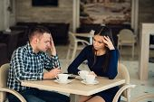 Young couple arguing in a cafe. She's had enough, boyfriend is apologizing. Relationship problems poster