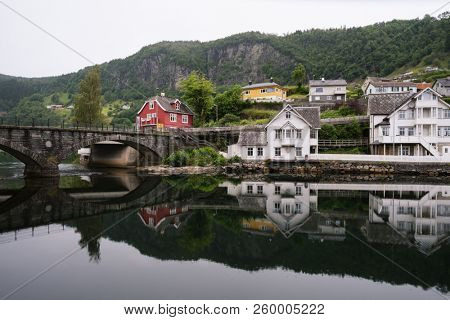 Norheimsund - Norwegian city near the fjord of Hardangerfjord, Norway. Old stone bridge. Mirror reflection in water. Overcast northern weather