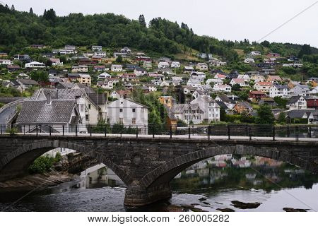 Norheimsund - Norwegian city near the fjord of Hardangerfjord, Norway. Old stone bridge over the water. Overcast northern weather