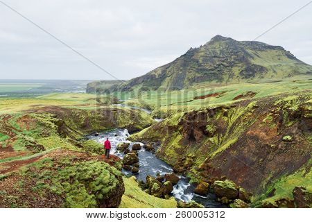 Hiking along the Skoga River, Iceland. Scenic landscape near the Skogafoss Falls. Tourist enjoys a beautiful view of the valley