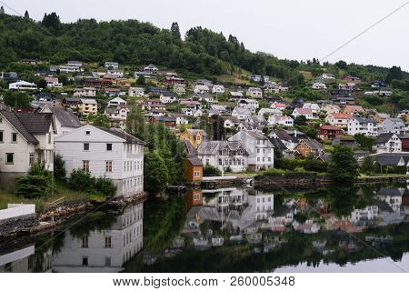 Norheimsund - Norwegian city near the fjord of Hardangerfjord, Norway. Overcast northern weather. Mirror reflection in water