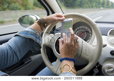 Bottrop, Germany - Aug 16, 2018: A Blond Woman Is Whatsapping On Her Smartphone While She Is Driving