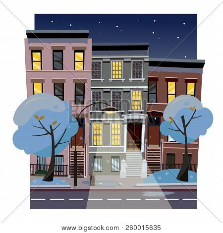 Flat Cartoon Vector Illustration Of Winter Snowy City Street At Night. Uneven Houses With Luminous W