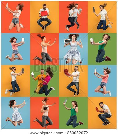 Jump Of Young Women And Man Over Colorful Studio Background Using Laptop Or Tablet Gadget While Jump