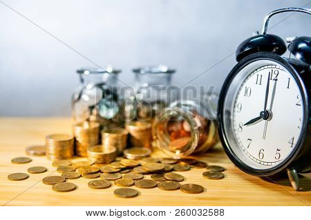 Clock With Coins In Currency Glass Jars And Spilling On Wooden Table. Saving Money For Future Retire