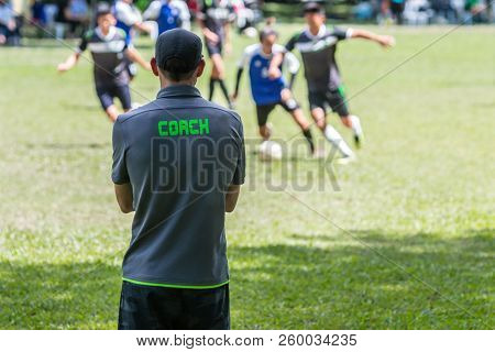 Male Soccer Or Football Coach In Gray Shirt With Word Coach Written On Back, Standing On The Sidelin