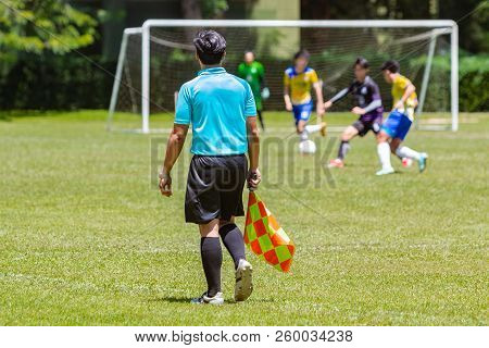 Soccer Or Football Lineman Referee Watching Action In A Boy Youth Game Playing In A Soccer Field On