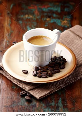 Cup of Cafe Crema. Espresso cup and coffee beans. Brown, rustic background. Close up.