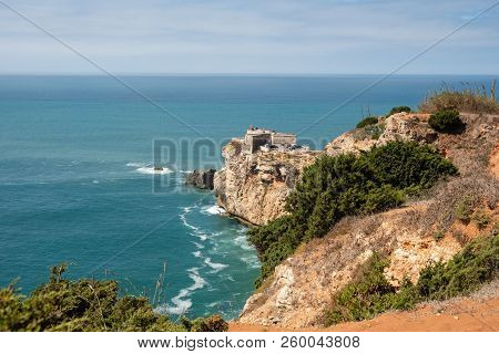 Nazare, Portugal - September 20, 2018 : On The Cliffs Of Yellow Stone The Lighthouse Of The Nazare,