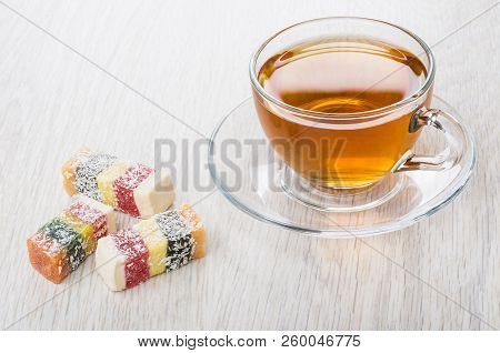 Multicolor Rakhat-lukum And Cup Of Tea On Saucer On Wooden Table
