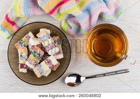 Multicolor Rakhat-lukum In Brown Saucer, Cup Of Tea, Teaspoon, Napkin On Wooden Table. Top View