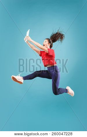 Gadget In Modern Life. Jump Of Young Woman Over Pink Studio Background Using Laptop Or Tablet Gadget