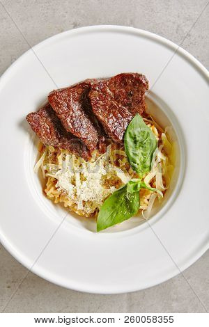 Mushrooms Risotto with Grilled Slices of Beef in White Plate Top View. Traditional Italian Creamy Arborio Rice with Well Done Veal and Green Basil