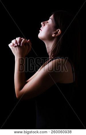 Faithful woman praying, hands folded in worship to god with head up and closed eyes in religious fervor, on a black background. Concept for religion, faith, prayer and spirituality.