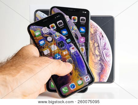 Paris, France - Sep 25, 2018: Man Hand Holding The Two New Iphone Xs And Xs Max Smartphone Model By