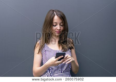 Waist-up Portrait Of Brunette Young Female Holding Telephone And Messaging. Good-looking Model In St