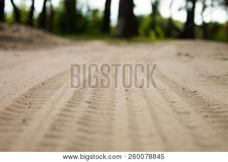 Tires Marks On Sand Close Up Image. Textured Tire Tracks On Sand Closeup. Industrial Background. Rib